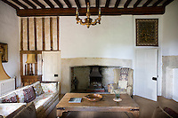 Although simply furnished with contemporary pieces the living room's Tudor legacy is obvious from the exposed Tudor beams and stone fireplace