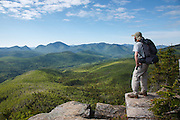 Zealand Notch  - A hiker takes in the view of the Pemigewasset Wilderness from the summit of Zeacliff during the summer months. This view point is along the Appalachian Trail in the White Mountains, New Hampshire. Much of this forest was logged during the East Branch & Lincoln Railroad era, which as was a logging railroad in operation from 1893-1948.