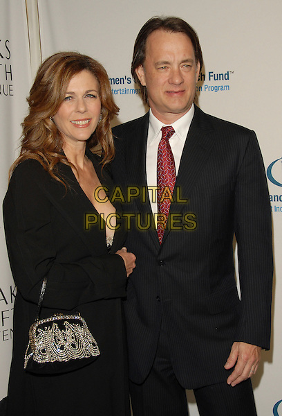 RITA WILSON & TOM HANKS.The Saks Fifth Avenue's Unforgettable Evening benefiting The EIF Women's Cancer Research Fund,Honoring Melissa Etheridge held at The Regent Beverly Wilshire Hotel in Beverly Hills, California, USA..March 1st, 2006.Ref: DVS.half length celebrity couple married husband wife black suit jacket purse jewel encrusted.www.capitalpictures.com.sales@capitalpictures.com.Supplied By Capital PIctures