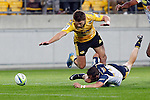 Hurricanes' hooker Dane Coles, top, dives over ACT Brumbies' wing Robbie Coleman in order to recover the loose ball in the Super Rugby match at Westpac Stadium, Wellington, New Zealand, Friday, March 07, 2014. Credit: Dean Pemberton