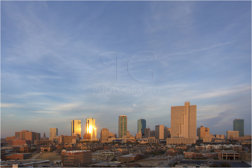 Early evening in Fort Worth, Texas brings cold weather and a rising moon in the East. In the distance, you see the high rises including (from left to right) the Tarrant County Courthouse, the Wells Fargo Tower, the D R Horton Tower, the Fort Worth Tower, the Carter and Burgess Tower, the Burnett Plaza, the AT&T Building, and the Omni Fort Worth.