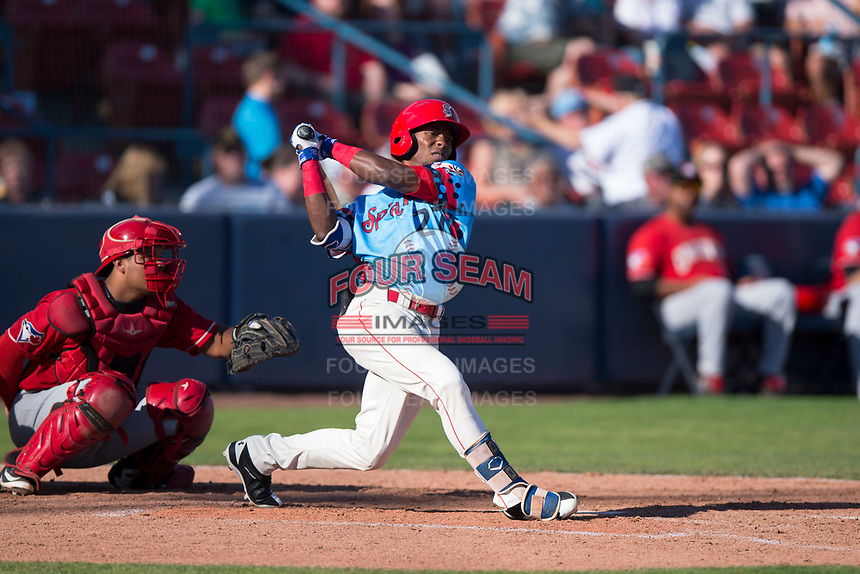 Spokane Indians center fielder Julio Pablo Martinez (27) follows through on his swing in front of catcher Yorman Rodriguez (13) during a Northwest League game against the Vancouver Canadians at Avista Stadium on September 2, 2018 in Spokane, Washington. The Spokane Indians defeated the Vancouver Canadians by a score of 3-1. (Zachary Lucy/Four Seam Images)