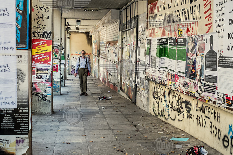 ATHENS, GREECE: a man walks in a street covered with graffitti and posters.