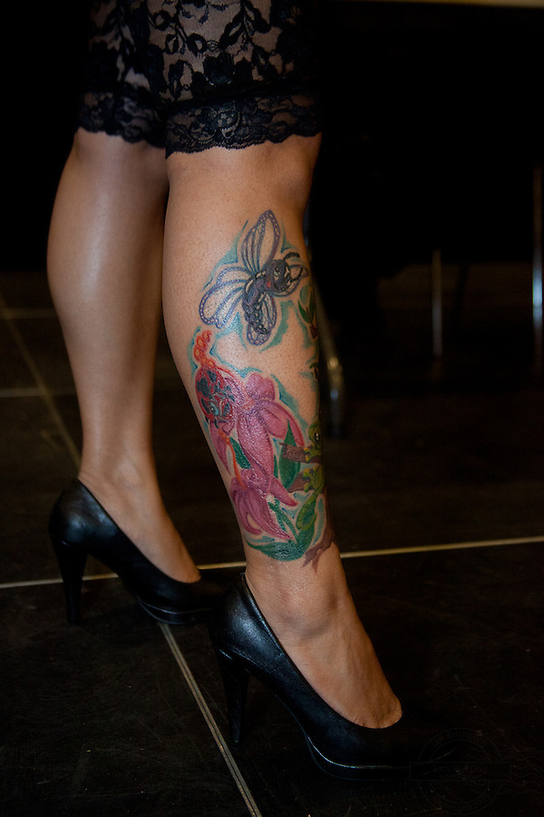 Tattoo Convention in Kolding 2011. Arranged by BodyMod.dk<br /> Young woman with flowers and insects on leg.