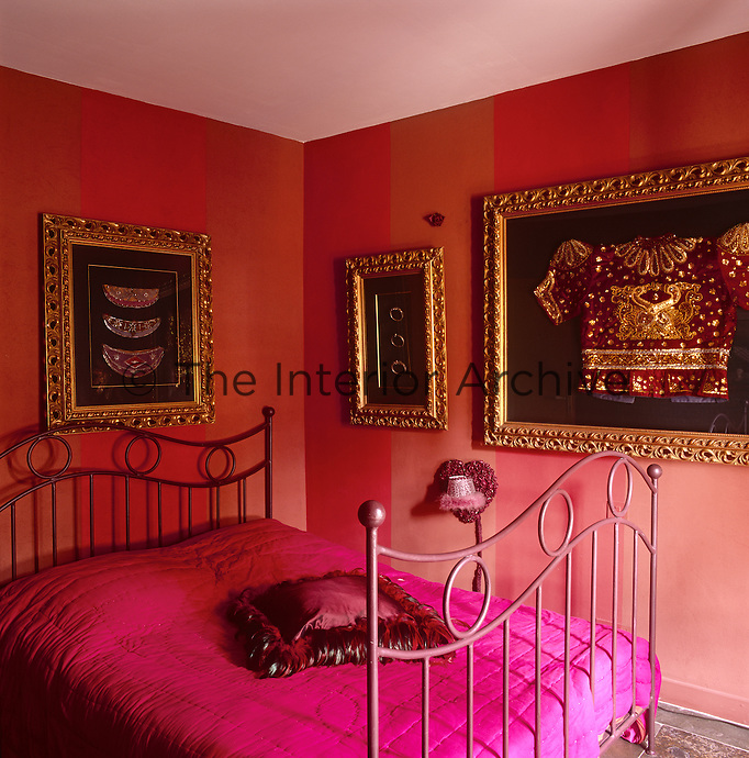 A red bedroom with a metal bed that has a shocking pink cover. A richly embroidered jacket and other items are displayed in gilt frames.