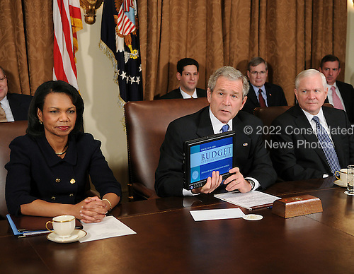 Washington, D.C. - February 4, 2008 -- United States President George W. Bush holds a computer with the entire United States budget for fiscal year 2009 on it as he discusses his 3 trillion dollar budget plan after meeting with his cabinet in the Cabinet Room of the White House in Washington, D.C. on Monday, February 4, 2008.  The budget features an approximate 400 billion dollar deficit of which his 145 billion dollar economic stimulus plan is a part. From left to right: United States Secretary of State Condoleezza Rice; President Bush; and Secretary of Defense Robert Gates..Credit: Ron Sachs / Pool via CNP