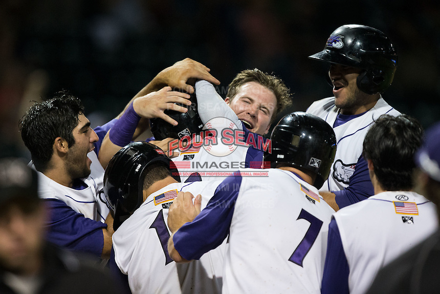 Keon Barnum (center) of the Winston-Salem Dash is mobbed by his teammates after scoring the winning run on a wild pitch in the bottom of the ninth inning against the Myrtle Beach Pelicans at BB&T Ballpark on August 20, 2015 in Winston-Salem, North Carolina.  (Brian Westerholt/Four Seam Images)