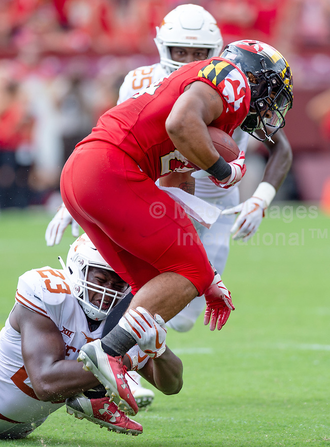 Landover, MD - September 1, 2018: Maryland Terrapins running back Ty Johnson (24) is tackled by Texas Longhorns linebacker Jeffrey McCulloch (23) during game between Maryland and No. 23 ranked Texas at FedEx Field in Landover, MD. The Terrapins upset the Longhorns in back to back season openers with a 34-29 win. (Photo by Phillip Peters/Media Images International)