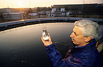 Man holding sample of Po River water that is part of the Turin, Italy water supply system.