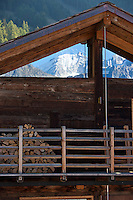 The snow-capped peak of Mont Blanc is reflected in the windows fitted beneath the eaves of this rustic chalet