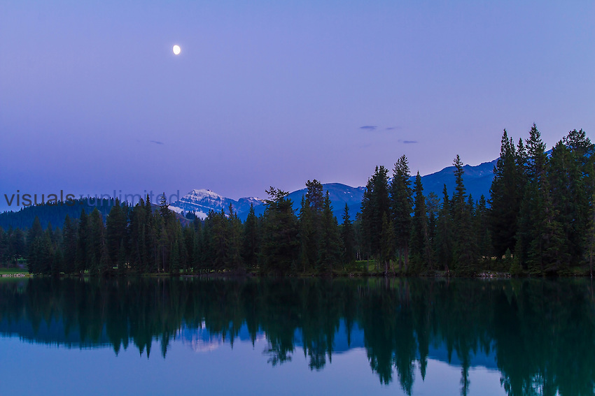 Gibbous Moon over Lac Beauvert, Jasper National Park, Canada in summer twilight. Snow-covered peak is Mt. Edith Cavell.