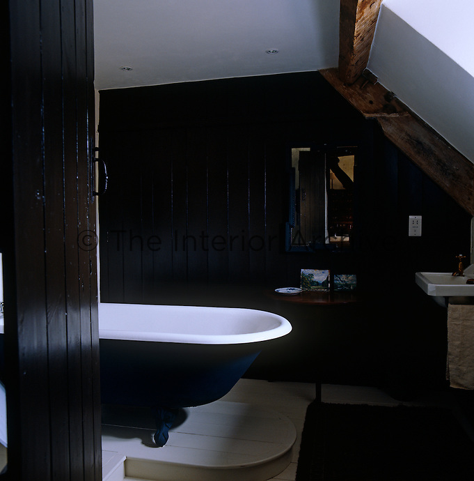 The wooden tongue-and-groove in the bathroom have been painted black to match the sides of the roll top bath resulting in a dramatic decorative scheme of black-and-white