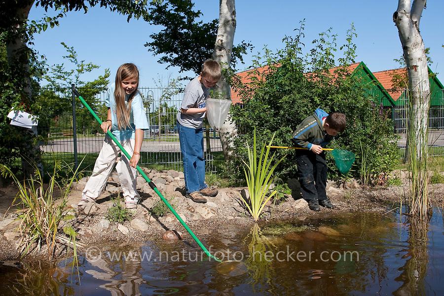 Grundschulklasse, Schulklasse im Schulgarten an ihrem selbst angelegtem Schulteich, Schul-Teich, Gartenteich, Garten-Teich, Kinder keschern im Teich, Exkursion am Teich, Biologie-Unterricht im Freien, Grünes Klassenzimmer