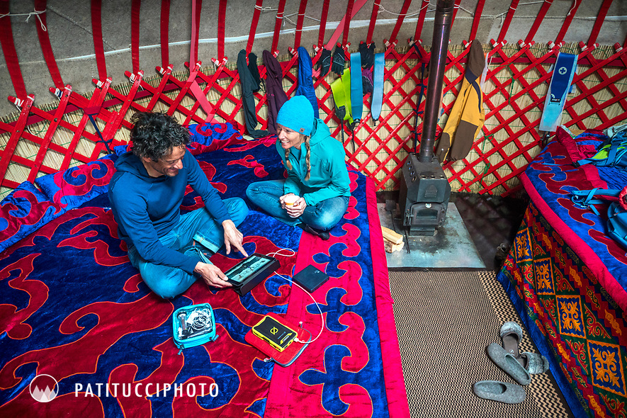A couple sits inside a yurt using an iPad and battery pack while traveling in Kyrgyzstan