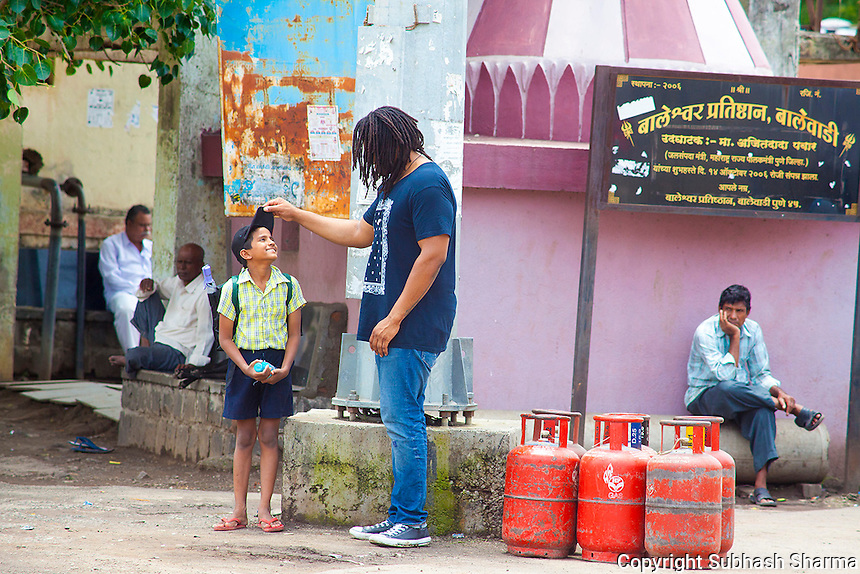 14 July 2016 - Pune - INDIA.<br /> Jamal Idris interacts with a school kid on way to school on the streets of Balewadi village at Pune.<br /> <br /> (Subhash Sharma for the Sunday Telegraph)