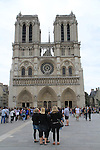Girls standing in front of Notre Dame Cathedral in Paris, France.