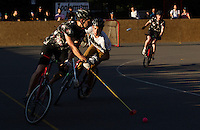 17 AUG 2014 - LONDON, GBR - A player from Triple Jay (in black) races up the court during the game against Partisans at the 2014 London Open Bike Polo tournament in Highbury Fields in London, Great Britain (PHOTO COPYRIGHT © 2014 NIGEL FARROW, ALL RIGHTS RESERVED)