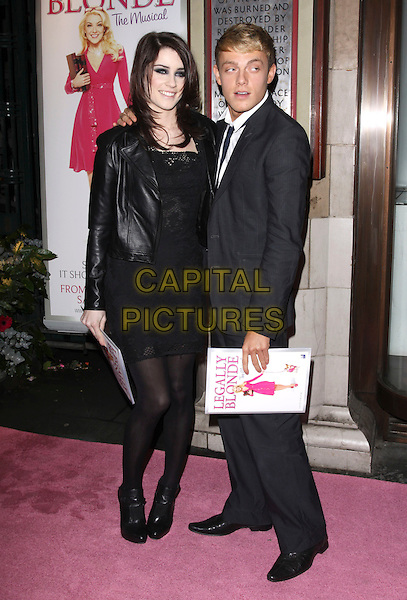 "LUCIE JONES & GUEST .Attending the ""Legally Blonde"" musical Gala Performance, Savoy Theatre, London, England, UK, .13th January 2010. .Full length black leather jacket lace dress tights ankle boots .CAP/AH.©Adam Houghton/Capital Pictures."