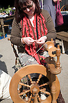 Woman demonstrating traditional spinning at a country craft event, Shottisham, Suffolk, England