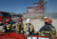 NWA Democrat-Gazette/ANDY SHUPE<br /> Fire captains, firefighters and training officers watch Wednesday, March 7, 2018, as they wait for their turn to participate in a training workshop for fire department leadership to meet current National Fire Protection Association standards at the Fayetteville Fire Department training facility in south Fayetteville. Thirty students and instructors from agencies in seven states attended the training meant to train department training officers at current standards.