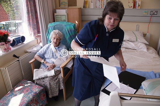 Nurse with disability consulting elderly patient's medical notes in hospital,