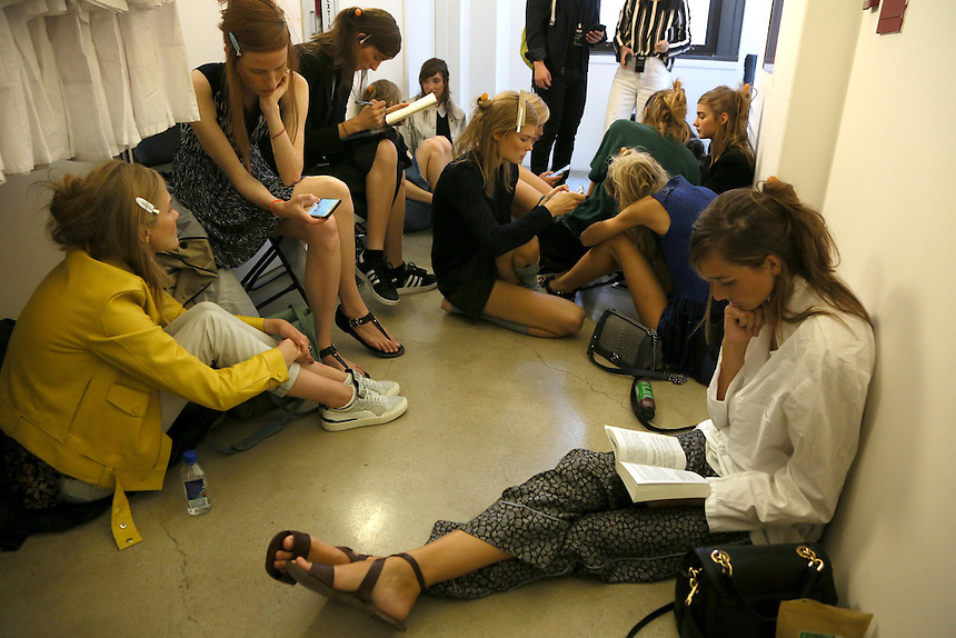 Models relax backstage before being called for dressing at the Michael Kors presentation at New York Fashion Week in New York, Wednesday, September 16, 2015. AFP PHOTO/TREVOR COLLENS