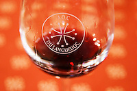 A wine tasting glass against a red background filled with red wine, the glass engraved with a circle and the text AOC du Languedoc, and the Languedocien Cathar cross, detail