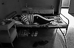 "A patient sleeps in a room that can accommodate six occupants of both genders in a psychiatry ward of a county hospital in Bulgaria, on August 03, 2006. He says the mattress underneath him is at least ten years old, and he complains it is difficult to sleep on it because it is ""infested with fleas."" All of his belongings -- including clothes, shoes, food utensils and bed sheets -- he brought from home because the hospital could not provide any of them."