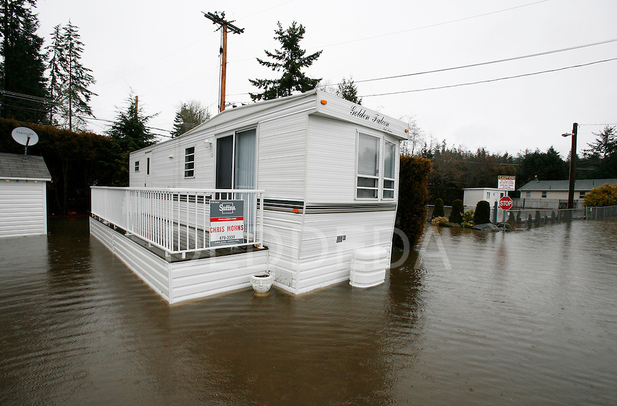 A mobile home, that is for sale, sits in a pool of water after flooding due to heavy rainfall at Otter Point Resort west of Sooke, British Columbia, on Vancouver Island. Roads were closed in some areas due to the flooding. Photo assignment for the Globe and Mail national newspaper in Canada.