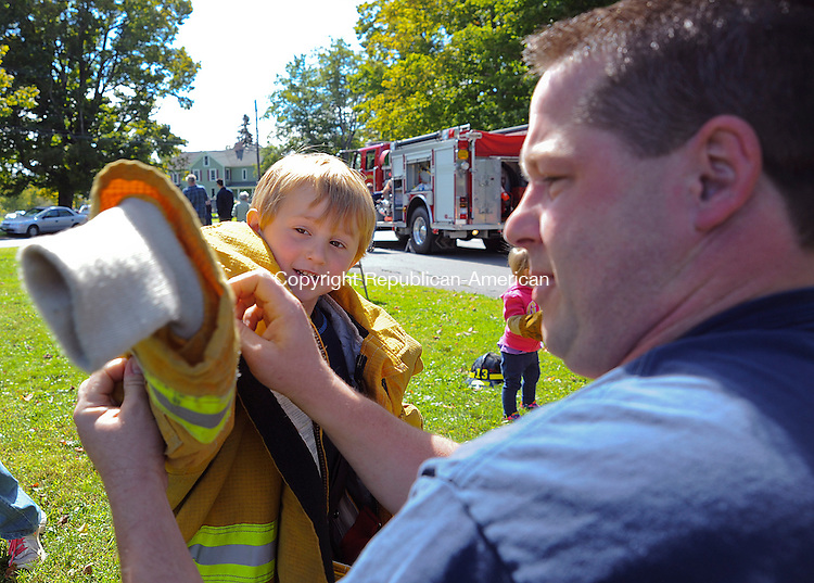 WINSTED, CT 14 SEPTEMBER 2013--091413JS07-Joseph Sugerak, 3, of Torrington, gets a hand from Winchester Center volunteer firefighter Bryan Collin, as he gets dressed in turnout gear during Winchester Center Day on Saturday in Winchester Center. The event was sponsored by the Winchester Center Congregational Church, Winchester Grange #74, the Winchester Center Volunteer Fire Department and the Winchester Center Historical Association. <br /> Jim Shannon Republican American