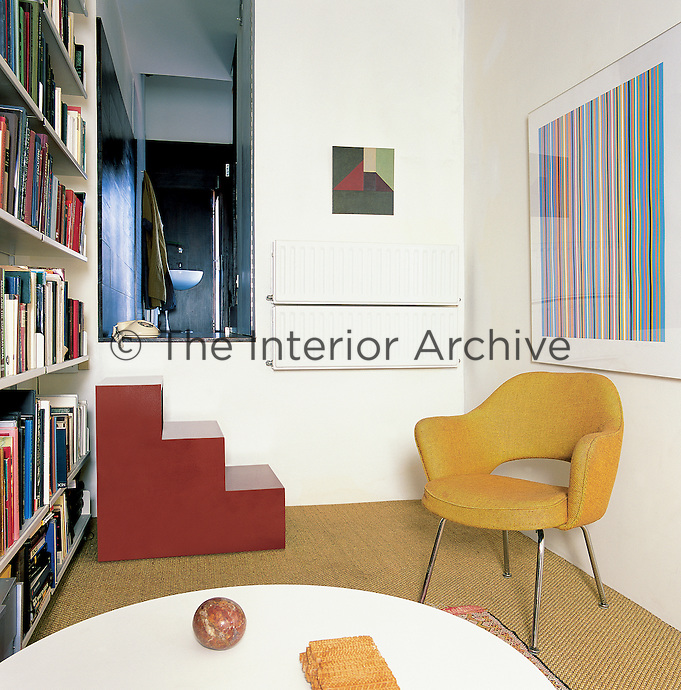 A library/sitting room with steps up to an aperture leading to a bathroom. The silkscreen is by Bridget Riley, gesso painting by Chung Eun Mo and moquette by Maud Cotter. The tweed and chrome chair is by Eero Saarinen, the coffee table by Charles and Ray Eames.