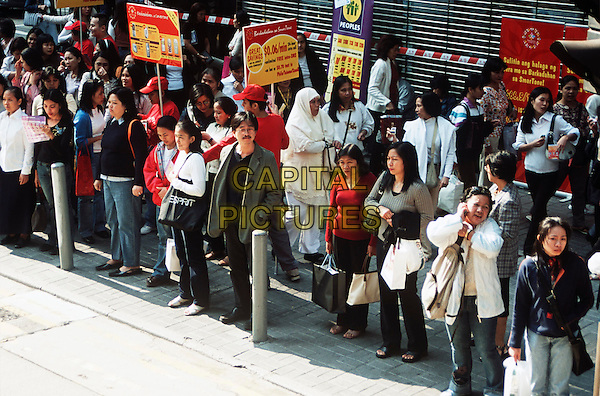 People standing on a pavement, Hong Kong, China