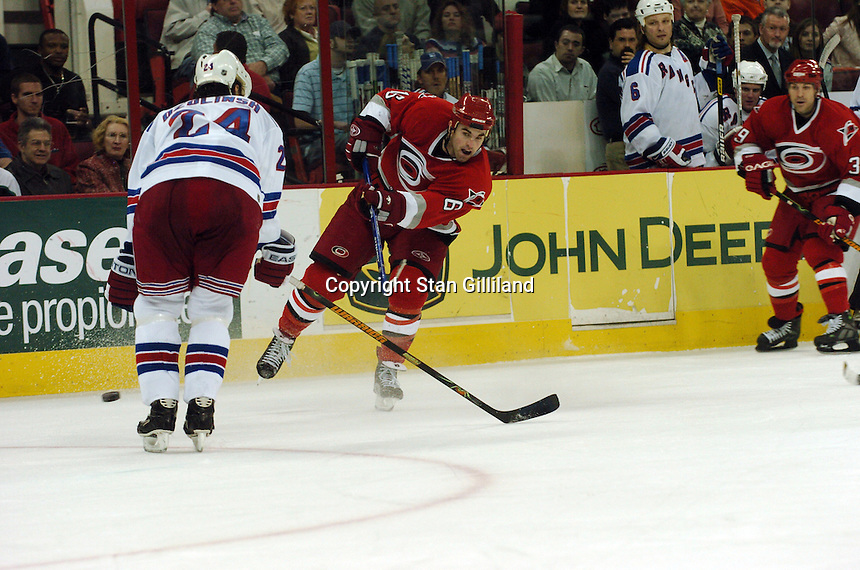 Carolina Hurricanes' Andrew Ladd, center, shoots and hits the New York Rangers' Sandish Ozolinsh, left, Tuesday, March 14, 2006 at the RBC Center in Raleigh, NC. Carolina won 5-3.