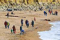 BNPS.co.uk (01202 558833)<br /> Pic: Graham Hunt/BNPS<br /> <br /> Visitors not put off by the coronavirus pandemic flock to the seaside resort of West Bay in Dorset on a day of sunshine and clear blue skies.<br /> <br /> Visitors walking on the beach.