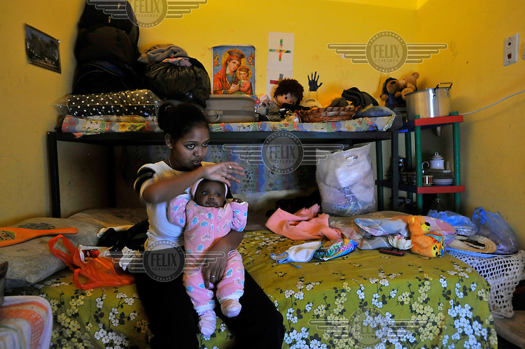A woman holds her baby as she watches TV, sitting at her room in a compound of Eritrean asylum seekers.