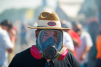 Jun 11, 2017; Englishtown , NJ, USA; NHRA fan wears a gas mask to protect from the nitro methane fuel fumes as cars warm up in the pits during the Summernationals at Old Bridge Township Raceway Park. Mandatory Credit: Mark J. Rebilas-USA TODAY Sports