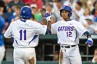 Florida Gators shortstop Richie Martin (12) greets teammate Josh Tobias (11) after scoring against the Miami Hurricanes in the NCAA College World Series on June 13, 2015 at TD Ameritrade Park in Omaha, Nebraska. Florida defeated Miami 15-3. (Andrew Woolley/Four Seam Images)