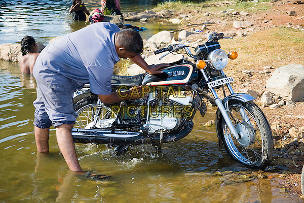 Man washing a motorcycle in a river, Madurai, Tamil Nadu, India