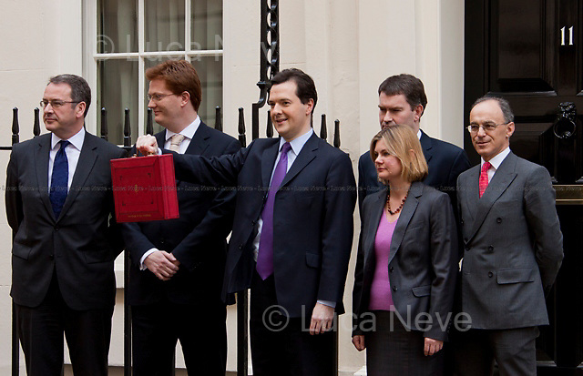 "London, 23/03/2011. UK Prime Minister David Cameron leaves 10 Downing Street on Budget Day. He is followed by  the Chancellor of the Exchequer, George Osborne, who (followed by his team) shows the ""red box"" (Budget Box) containing the Budget for the fiscal year. In the meanwhile, outside the gates of Downing Street, protesters gather for a variety of demonstrations. The demands of protestors included an end to the Government budget cuts and austerity measures and a stop to cuts in the NHS."