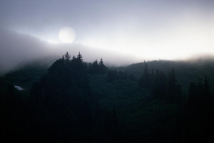 The setting sun peeks through fog wafting through the Kenai Mountains above Seward, Alaska.