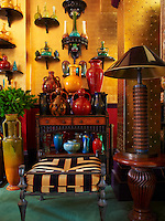 A collection of 19th century pottery is displayed on wooden brackets on gilded walls and on other flat surfaces in the living room