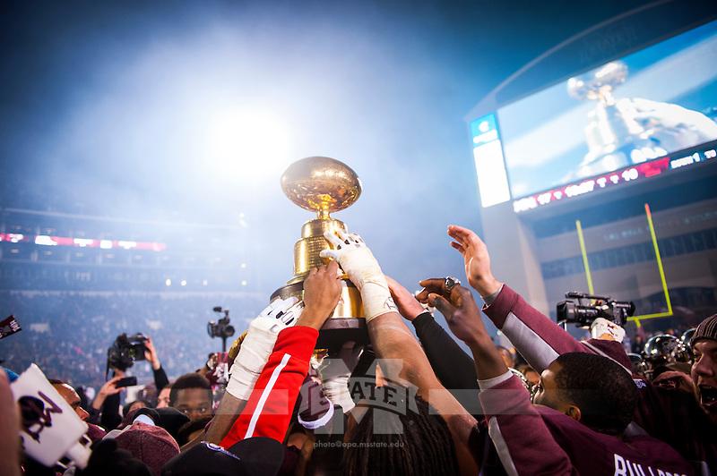 Hoisting the Egg Bowl Trophy (photo by Russ Houston / © Mississippi State University)