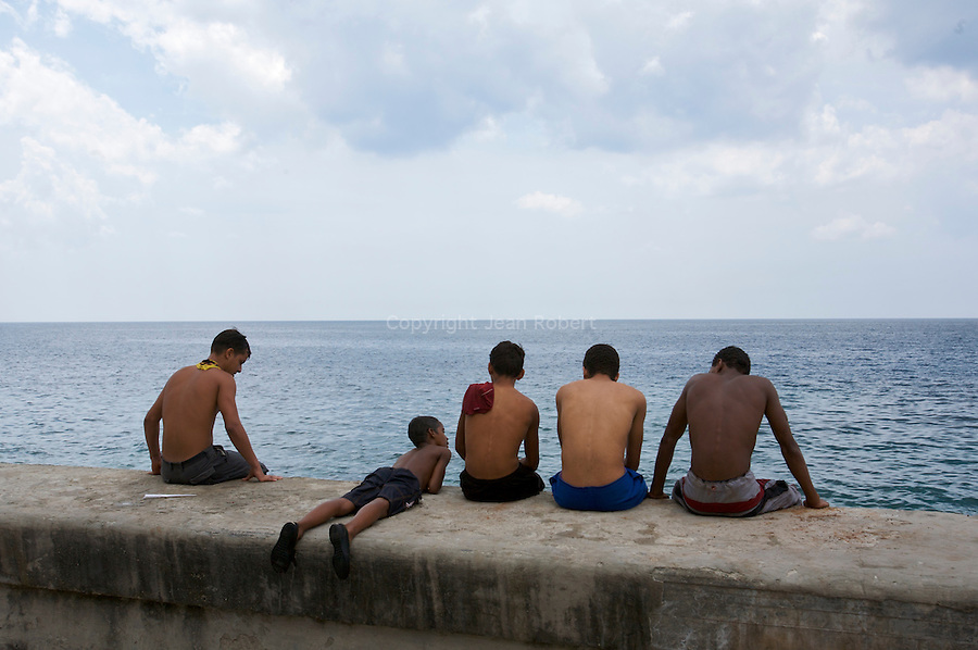 Young men looking at the ocean on the Malecon.La Habana