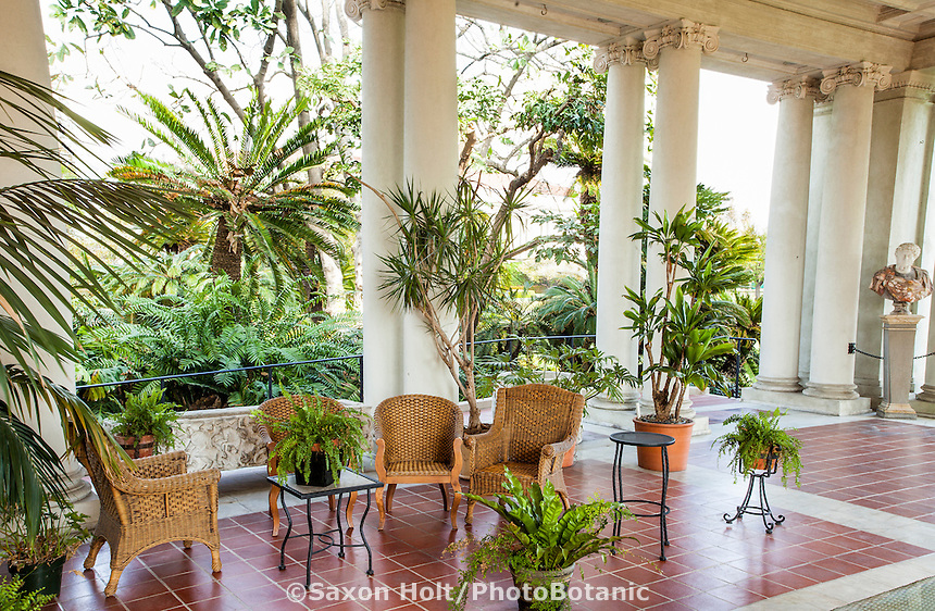 Wicker patio furniture on polished tile floor of luxurious outdoor room veranda of estate garden