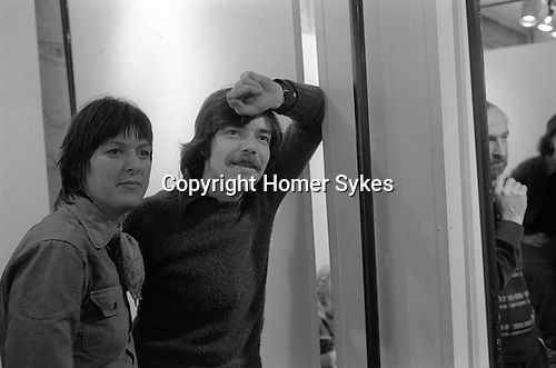 """The Photographers Gallery Great Newport Street London 1971. """"Co Optic""""  Christmas Print Auction. Pete Turner and wife to be Heather Forbes. Pete was editor of Creative Camera. He died in New Zealand in the 1990's. Howard Jeffs with hand to chin."""