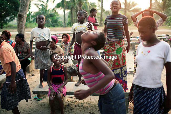 KINSHASA, DEMOCRATIC REPUBLIC OF CONGO - JULY 6: Esther Yandakwa (l), age 9, watches as her friend Betty Nginamawu (c), age 14, dance among friends at a yearly summer camp run by Orper, a local NGO on July 6, 2006 in N Djili outside Kinshasa, Congo, DRC. The NGO has several shelters for homeless boys and girls in Kinshasa and has a program that reunites children with their families. The capital has a growing problem with children displaced by war, poverty and many has been rejected by their families and forced on the streets. About 15,000 children are estimated to live on the streets of Kinshasa. About fifty girls got to spend a week relaxing, playing, swimming eating three meals a day. Most important of all, it took them off the hard streets of Kinshasa, where they are often abused, take drugs and forced into prostitution. Esther has lived on the streets for a few years and run away from her family. She abuse drugs, alcohol and works as prostitute. Congo, DRC is in ruins after forty years of mismanagement by the corrupt dictator and former president Mobuto Sese Seko. He fled the country in 1997 and a civil war started. The country is planning to hold general elections by July 2006, the first democratic elections in forty years. (Photo by Per-Anders Pettersson)