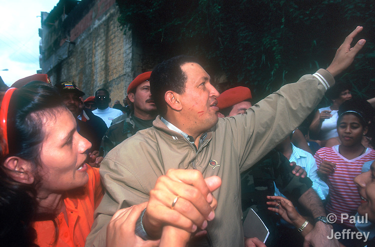 Venezuelan President Hugo Chavez during a visit to the Caracas neighborhood of Catuche in January 2000 following Dec 1999 flooding. Note lipstick on Chavez' face from kisses from women supporters.