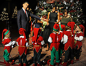 United States President Barack Obama (L) points to a child dressed in a Christmas elf costume as they gather for a group photo with First Lady Michelle Obama at a Christmas In Washington celebration at the Building Museum in Washington, DC, USA, Sunday, December 12, 2010.  Michelle Obama's mother Marian Robinson is at (R). .Credit: Mike Theiler - Pool via CNP