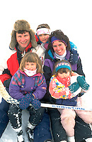 Family resting on winter ice skating rink age 35 the children ages 3 through 6. Brackett Park Minneapolis  Minnesota USA
