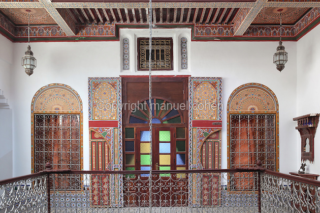 First floor central courtyard area with a bedroom door and windows with painted wooden panels off the balustraded balcony, in a typical Tetouan riad, a traditional muslim house built around a courtyard, built in Moorish style with strong Andalusian influences, next to the Great Mosque or Jamaa el Kebir in the Medina or old town of Tetouan, on the slopes of Jbel Dersa in the Rif mountains of Northern Morocco. Tetouan was of particular importance in the Islamic period from the 8th century, when it served as the main point of contact between Morocco and Andalusia. After the Reconquest, the town was rebuilt by Andalusian refugees who had been expelled by the Spanish. The medina of Tetouan dates to the 16th century and was declared a UNESCO World Heritage Site in 1997. Picture by Manuel Cohen